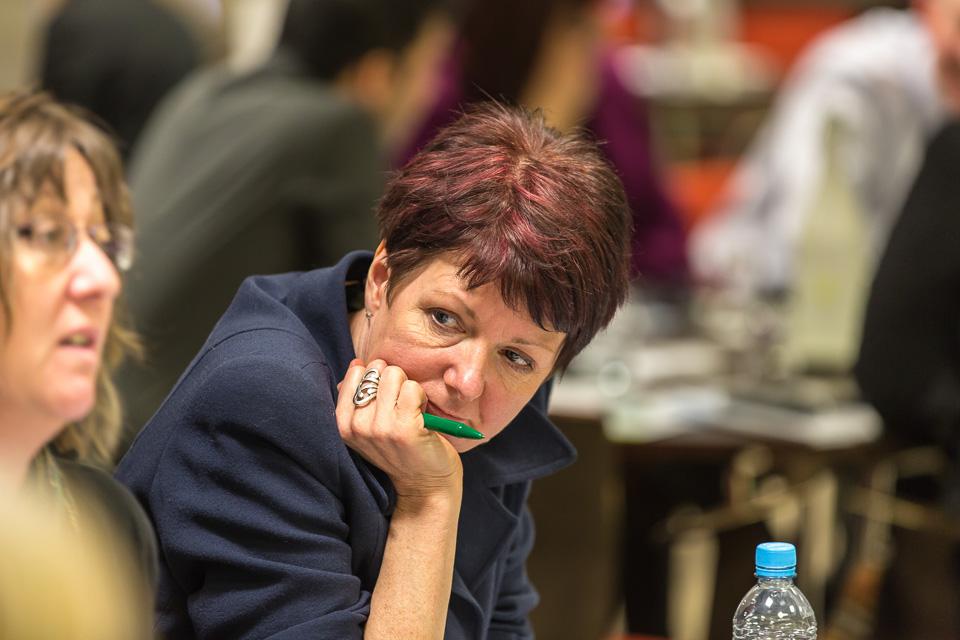 Delegate looking left holding pen