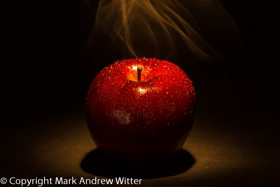Red apple and smoke with black background