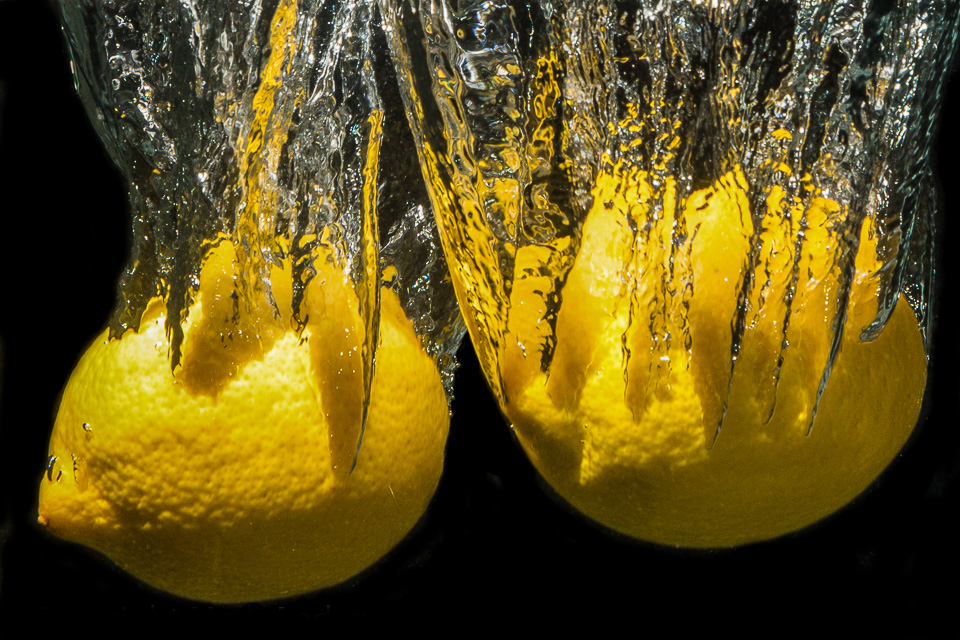 two lemon dropping into water