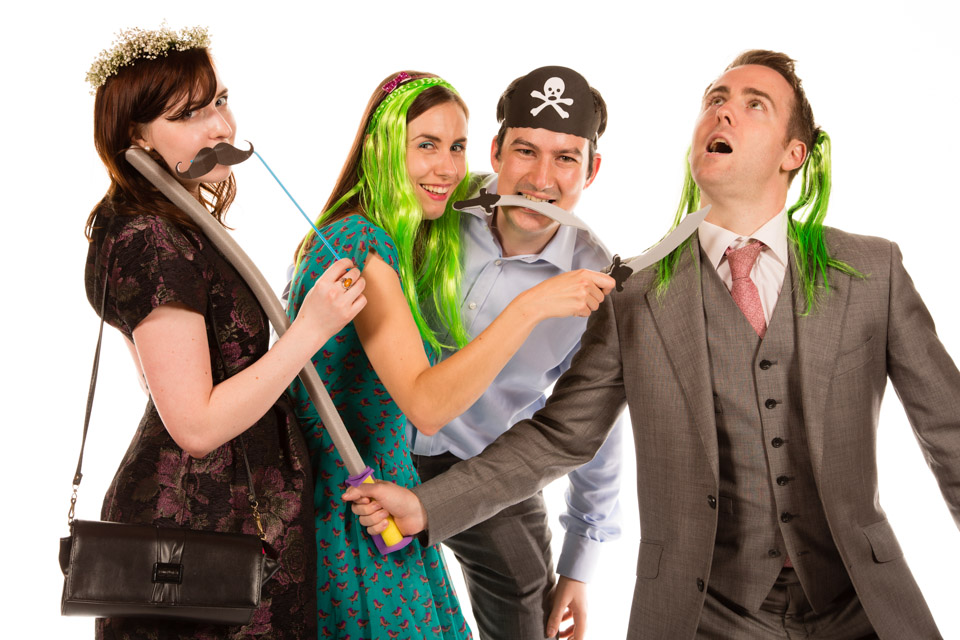 four people with fancy dress wigs and sword