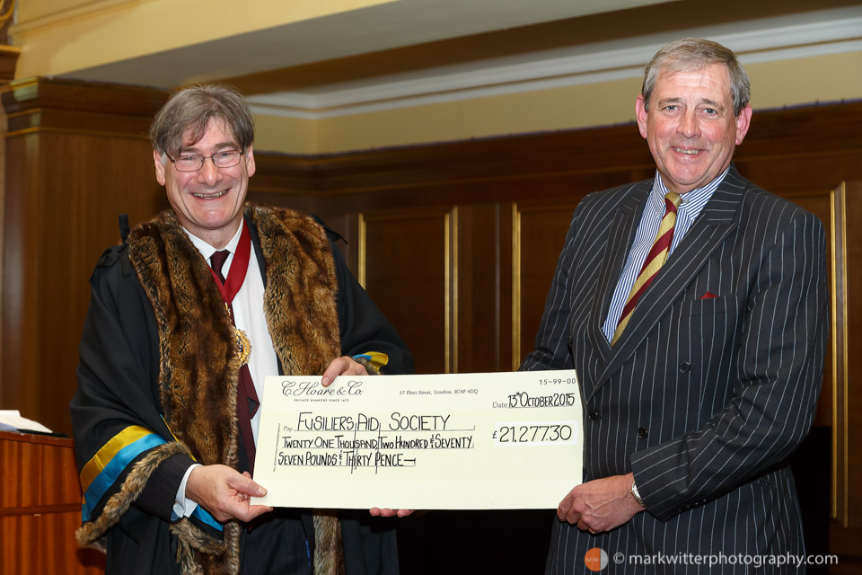 Colonel Nigel Easton QVRM TD of the Royal Fusiliers - (City of London Regiment) receives a cheque from John Rubinstein Master of the Cordwainers Company 2015 at the Cordwainers Fusiliers Dinner at the Clothworkers Hall.