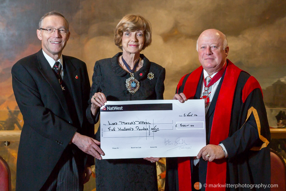 Dame Fiona Woolf DBE JP Lord Mayor of London 2013-14 receives a cheque at the Guildhall for the Lord Mayor's appeal from Colin Smith MBE BEM FIH Yeoman Warder at HM Tower of London and Chairman of the City of London Beadles' Guild 2014.