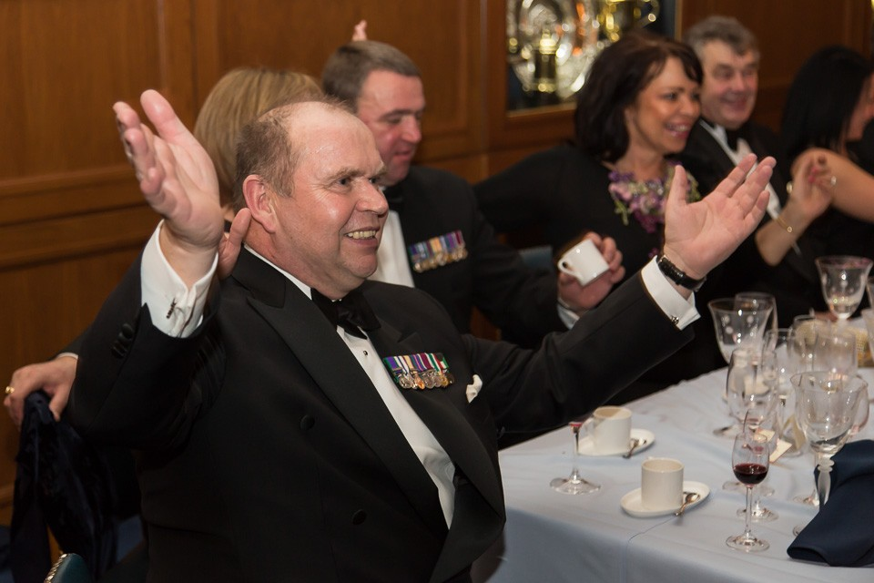 man with hands held up at Beadles' Guild Dinner