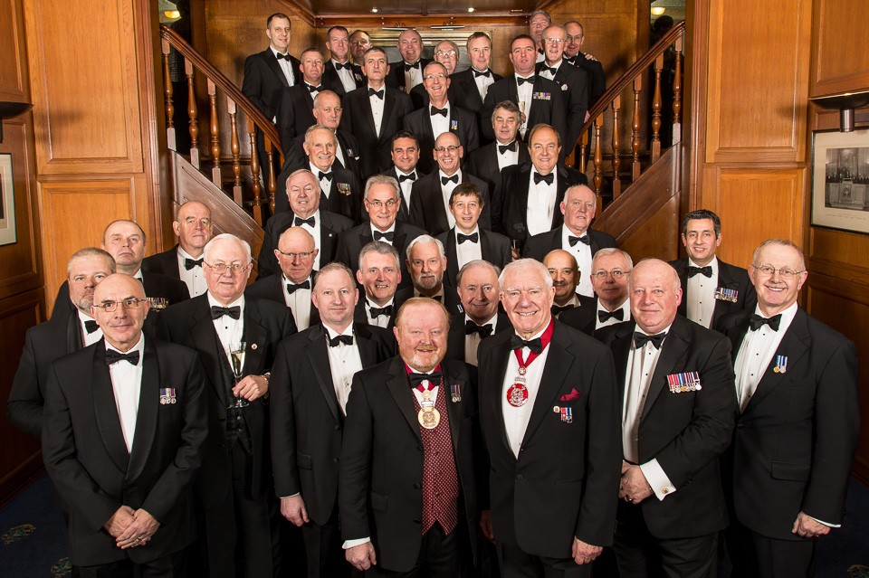 large group of men in dinner jackets in stairs