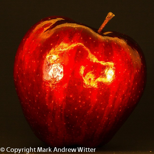 Red apple standing on black surface